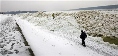 People walk by piles of broken ice on the Danube river in Belgrade February 20, 2012. REUTERS/Ivan Milutinovic