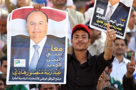 A man carries a poster of Yemen's Vice President Abd Rabbu Mansour Hadi during an election rally in Sanaa February 20, 2012. REUTERS/Mohamed al-Sayaghi