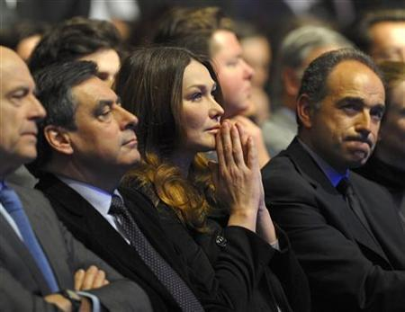 France's First Lady Carla Bruni-Sarkozy(C) listens to her husband France's President Nicolas Sarkozy as he addresses his first major re-election campaign rally in Marseille, southern France, February 19, 2012. REUTERS/Philippe Wojazer