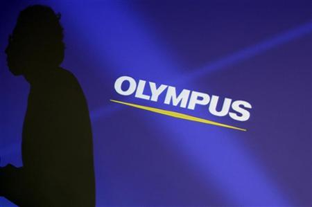 A staff member is silhouetted on a projector screen displaying a logo of Olympus Corp before a news conference in Tokyo February 13, 2012. REUTERS/Yuriko Nakao