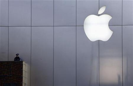 A policeman looks out from a balcony as the crowd is dispersed from the front of an Apple store in the Beijing district of Sanlitun January 13, 2012. REUTERS/David Gray