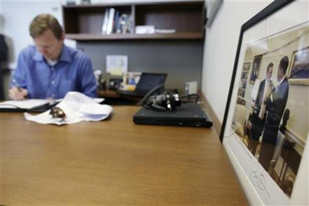 Campaign manager Jim Messina works inside President Barack Obama's new campaign headquarters in Chicago May 12, 2011, next to a photo of himself with the president. REUTERS/John Gress