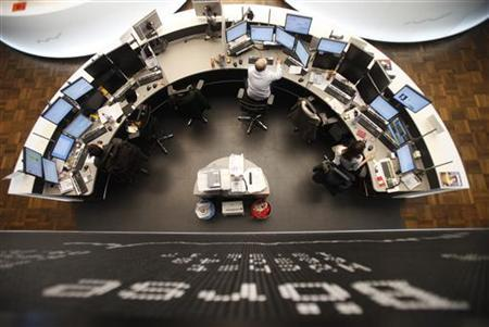 Traders work at their desks below the DAX board at the Frankfurt stock exchange February 1, 2012. REUTERS/Alex Domanski (GERMANY - Tags: BUSINESS)