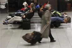 Passengers rest on chairs at the main terminal of Frankfurt's airport February 21, 2012. Strikes at Frankfurt airport, Germany's largest, will continue until the weekend, the GdF union, resulting in more flight cancellations and delays. Just under 200 apron control workers, such as those who guide aircraft to parking places, are striking over a pay dispute with Fraport, which runs the airport.    REUTERS/Alex Domanski (GERMANY - Tags: BUSINESS TRANSPORT EMPLOYMENT)