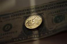 A Canadian Loonie, otherwise known as a one dollar coin, is displayed on top of an American one dollar bill in this posed photograph in Toronto, October 10, 2008.    REUTERS/Mark Blinch