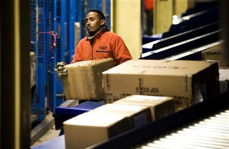 A wrkers loads parcels ready for transport at the global express company TNT's road hub in Duiven November 15 November, 2007.   REUTERS/Jerry Lampen (NETHERLANDS)
