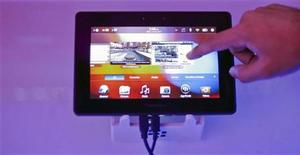 A conference attendee examines the BlackBerry PlayBook during its launch in Mumbai June 22, 2011. REUTERS/Danish Siddiqui