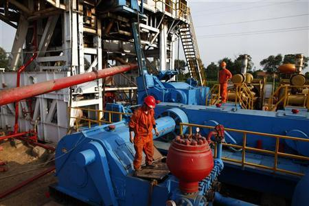 Men work on an oil rig at Sinopec's Shengli oil field in Dongying, Shandong province September 2, 2011. REUTERS/Aly Song