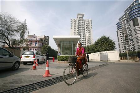 A woman cycles past an apartment complex where Tsutomu Omori, 49, who was head of Olympus's medical equipment business in India, was found dead in Gurgaon on the outskirts of New Delhi February 21, 2012. Omori, a top executive of Japan's scandal-ridden Olympus Corp has been found dead in a park outside New Delhi, an apparent suicide, The Times of India said on Tuesday, quoting police. REUTERS/Parivartan Sharma