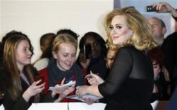 Multiple Grammy Award winner Adele signs autographs as she arrives for the BRIT Music Awards at the O2 Arena in London February 21, 2012.   REUTERS/Luke MacGregor