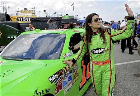 NASCAR Sprint Cup Series driver Danica Patrick (R) waves to fans while rolling her number 10 car out to the track before a practice session for the Daytona 500 at Daytona International Speedway in Daytona Beach, Florida February 18, 2012. REUTERS/Brian Blanco