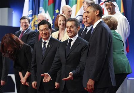 From 2ndL-R, China's President Hu Jintao, France's President Nicolas Sarkozy, and U.S. President Barack Obama react as G20 leaders take their places for the traditional family photo at the G20 Summit in Cannes, November 3, 2011. REUTERS/Chris Radcliffe/Pool