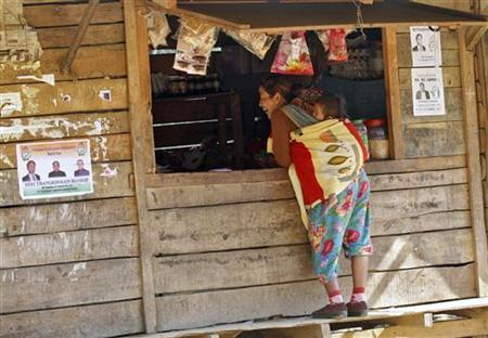 A woman laughs as she buys food from a shop where election posters are pasted on its wooden walls in Meelen village, Imphal January 23, 2012. REUTERS/Rupak De Chowdhuri