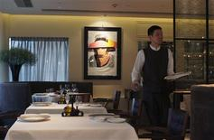 "A waiter walks past tables after arranging cutlery at Italian chef Umberto Bombana's restaurant in Hong Kong February 10, 2012. Bombana's distinctive flair for refined, regional Italian cuisine has taken him around the world and gained his Hong Kong restaurant three Michelin stars last year, within just two years of opening. After more than a year of soul-searching following the closing of the restaurant where he previously worked, Bombana  opened ""8 ½ Otto e Mezzo BOMBANA"" in Hong Kong's glitzy Central district. The name is a salute to the Italian movie by Federico Fellini. Picture taken February 10, 2012.       REUTERS/Andy Ho"