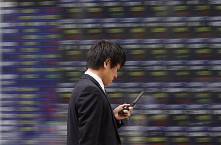 A man walks past a stock quotation board outside a brokerage in Tokyo October 24, 2011. REUTERS/Toru Hanai/Files