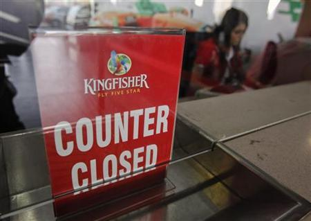 An employee of Kingfisher Airlines works next to a ''counter closed'' sign at their booking office at Mumbai's domestic airport February 20, 2012. REUTERS/Vivek Prakash
