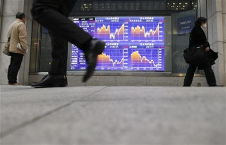The graphs of various market indices are displayed on an electronic board outside a brokerage in Tokyo February 15, 2012. REUTERS/Yuriko Nakao
