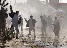 Демонстранты кидают камни в полицию около американской военной базы в Кабуле, 22 февраля 2012 года. США закрыли посольство в Кабуле из-за продолжающихся второй день массовых акций протеста, спровоцированных сожжением Корана на военной базе НАТО в Афганистане. REUTERS/Ahmad Masood