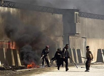 Afghan protesters set fire next to an unidentified foreign base in Kabul February 22, 2012. Several people were wounded on Wednesday, witnesses said, when shots were fired as hundreds of angry Afghans gathered in a second day of violent clashes after copies of the Koran, Islam's holy book, were burned at NATO's main base in Afghanistan. REUTERS/Ahmad Masood