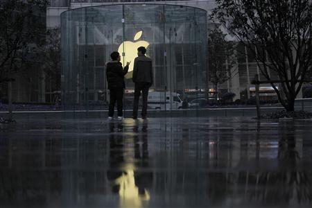 Two men stand in front of an Apple logo outside an Apple store in Shanghai February 22, 2012. A Shanghai court began hearing on Wednesday a case brought by a Chinese technology firm seeking to halt the sale of Apple Inc's iPads across the affluent Chinese city, accusing the U.S. firm of trademark infringement. REUTERS/Aly Song