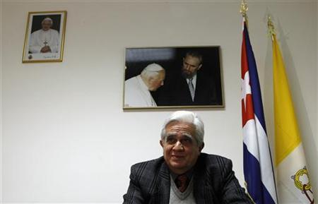Eduardo Delgado Bermudez, Cuba's ambassador to the Vatican, speaks in front of a picture of Pope John Paul II with Fidel Castro during an interview with Reuters TV at the Cuban embassy near the Vatican February 22, 2012. Pope Benedict wants to see Fidel Castro on his trip to Cuba next month but the meeting will depend on the health of the communist country's revolutionary leader, a senior Vatican official told Reuters on Saturday. REUTERS/Alessandro Bianchi