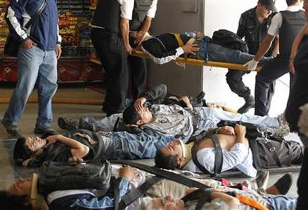 Commuters lie on stretchers after sustaining injuries when their train crashed into the Once station at rush hour in Buenos Aires February 22, 2012. REUTERS/Enrique Marcarian