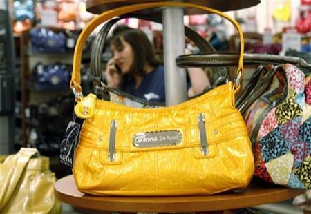 A shopper talks on her phone in the purse department of a store in Colorado, February 20, 2009.REUTERS/Rick Wilking