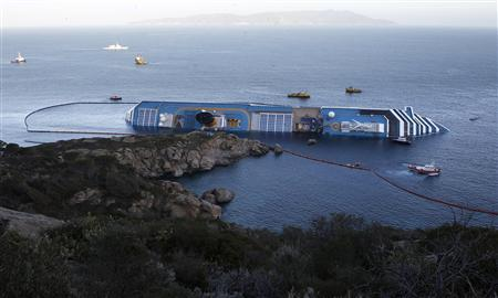 Oil recovery ships are seen around the Costa Concordia cruise ship which ran aground off the west coast of Italy at Giglio island in this January 21, 2012, file photo.  REUTERS/Giampiero Sposito/Files