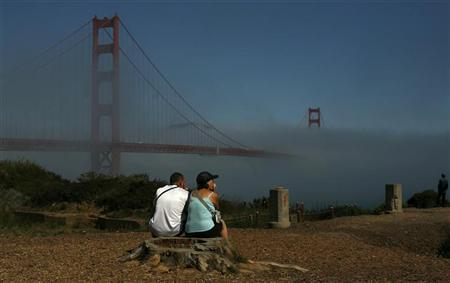 A couple looks out at the fog-shrouded Golden Gate Bridge in San Francisco, California August 23, 2011.  REUTERS/Robert Galbraith