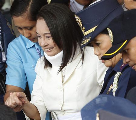 Former Philippine President Gloria Macapagal Arroyo leaves a local government building while being escorted by policemen after attending her court arraignment in Pasay city, Metro Manila February 23, 2012. Arroyo entered a plead of not guilty in the electoral fraud charges at a Manila regional trial court. REUTERS/Erik De Castro