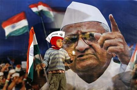 A boy holds a candle and the national flag in front of a portrait of anti-corruption activist Anna Hazare during a candlelight vigil in Ahmedabad December 27, 2011. REUTERS/Amit Dave/Files