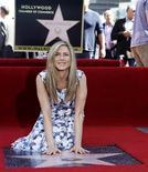 Atriz Jennifer Aniston toca sua estrela após ser descoberta na Calçada da Fama, em Hollywood, Califórnia. 22/02/2012   REUTERS/Mario Anzuoni