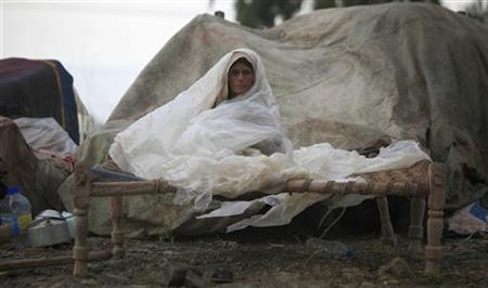 An Afghan refugee woman shields herself from rain as she sits on a ''charpoy'' (rope bed) while taking refuge along a road median in a village in Aza Khel, located in Pakistan's northwest Khyber-Pakhtunkhwa Province August 15, 2010. REUTERS/Fayaz Aziz/Files