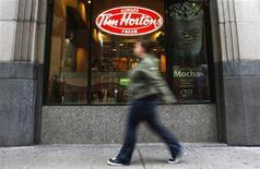A pedestrian walks past a Tim Hortons restaurant in Toronto October 26,  2007.  REUTERS/Mark Blinch