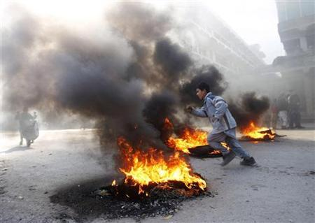 An Afghan boy runs next to fire during a protest in Jalalabad February 22, 2012. Gunfire wounded at least 26 people during fresh protests in several cities across Afghanistan over the burning of copies of the Koran, Islam's holy book, at NATO's main base in Afghanistan. REUTERS/Parwiz
