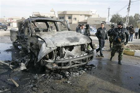Members of security forces stand guard at the site of a bomb attack in Kirkuk, 250 km (155 miles) north of Baghdad February 23, 2012. Two car bombs exploded in a quick succession in different districts wounding 20 people, including 15 policemen, in Kirkuk, police said.  REUTERS/Ako Rasheed (IRAQ - Tags: CIVIL UNREST)