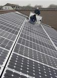 Workers install solar panels on the roof of a kindergarten in the town of Falkensee, near Berlin, in this December 10, 2008 file photo.      REUTERS/Erik Kirschbaum/Files  (GERMANY - Tags: ENERGY ENVIRONMENT BUSINESS)