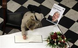 A woman signs a book of condolences in memory of late Irish comedian Frank Carson at City Hall in Belfast February 23, 2012. Carson died aged 85 at his home in Blackpool.   REUTERS/Cathal McNaughton