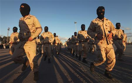Military members take part in a parade during the graduation of the first batch of volunteers in the special forces after joining the army, in Benghazi February 23, 2012. REUTERS/Esam Al-Fetori