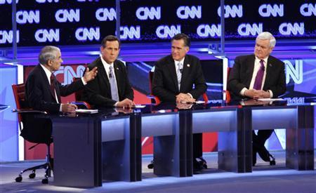 Republican presidential candidate Ron Paul speaks as Rick Santorum, Mitt Romney and Newt Gingrich look on during the Republican presidential candidates debate in Mesa, Arizona, February 22, 2012. REUTERS/Joshua Lott
