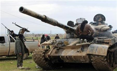 Free Syrian Army fighters look at a tank taken by defectors from the regular Syrian Army in Al Qusayr February 23, 2012. REUTERS/Samuel Jamison