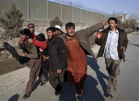 Afghan protesters carry a wounded man during clashes with the police in Kabul February 24, 2012. REUTERS/Ahmad Masood