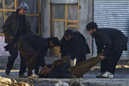 Afghan protesters move a dead man during clashes in Kabul February 24, 2012.  REUTERS/Ahmad Masood