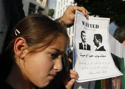 A Syrian girl living in Lebanon attends a protest with her father against Syrian President Bashar al-Assad during a sit-in demonstration in Beirut, February 24, 2012. REUTERS/Jamal Saidi
