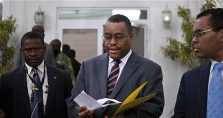 Newly appointed Haitian Prime Minister Garry Conille (C) reviews a document while leaving a news conference in Port-au-Prince October 6, 2011.  REUTERS/Swoan Parker