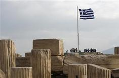 A Greek national flag flies at the archaeological site of the Acropolis Hill in Athens November 3, 2011.  REUTERS/John Kolesidis