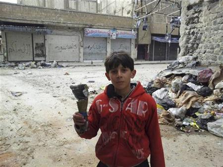 A boy holds the remain of a mortar in this handout picture taken by Syrian National Council (SNC) member Moulhem Al-Jundi in Karm Al Zaytoon, a neighbourhood of Homs, February 23, 2012.REUTERS/Moulhem Al-Jundi/Handout