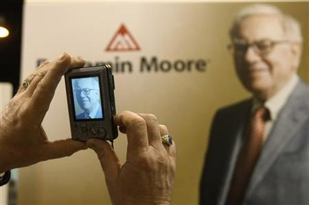 A shareholder takes a photo of a photo of Berkshire Hathaway Chairman Warren Buffett at the company trade show during the annual meeting in Omaha, Nebraska April 30, 2011. REUTERS/Rick Wilking/Files