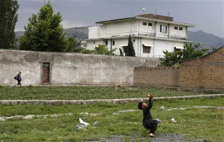 A boy plays with a tennis ball in front of the compound where U.S. Navy SEAL commandos killed al Qaeda leader Osama bin Laden in Abbottabad in this May 5, 2011 file photo. REUTERS/Akhtar Soomro/Files