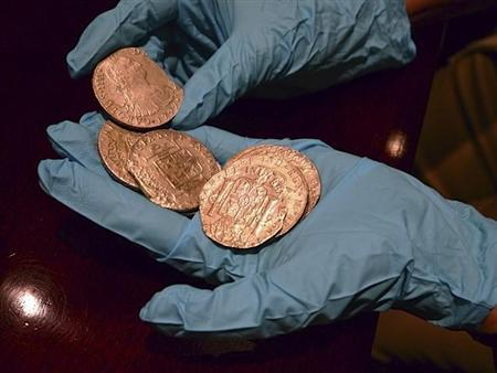 Gold coins from a treasure trove of gold and silver coins worth $500 million and recovered from a Spanish ship believed to be from the wreckage of the Nuestra Senora de las Mercedes, a ship sunk by the British Navy in 1804 as it returned from South America, are handled by a Spanish expert at an undisclosed warehouse in Sarasota, Florida in this handout photo released February 23, 2012.  REUTERS/Spanish Embassy/Handout